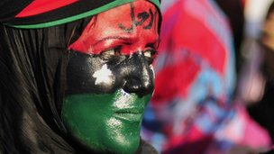 A woman attends a protest against Libyan leader Muammar Gaddafi in Benghazi in this June 29, 2011 file photo. 