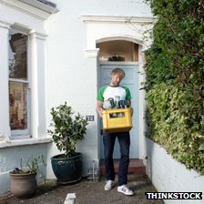Man carrying recycling box full of empty wine and beer bottles