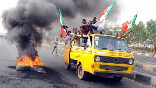People stand on a bus past a bonfire set up on Ikorodu Road, Lagos