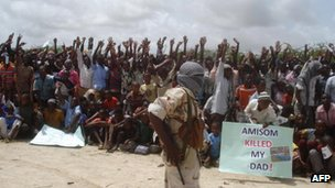 Somali men carry weapons during a demonstration organised by the Islamist al-Shabab group 5 July 2010