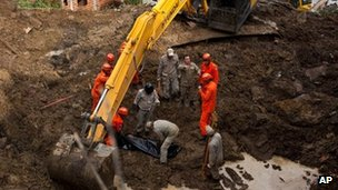 Rescue personnel recover the body of a mudslide victim in Jamapara, Rio de Janeiro state, Brazil, Tuesday 10 January  2012