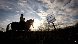 Riders from Crowberry Stables in Middleton, pass a sign marking a bridge on the proposed HS2 line near Middleton, Warwickshire