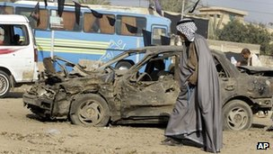A man walks past the scene of a car bomb attack in western Baghdad (10 January 2012)
