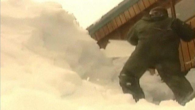 Man shovels huge pile of snow in Alaskan coastal town of Cordova.
