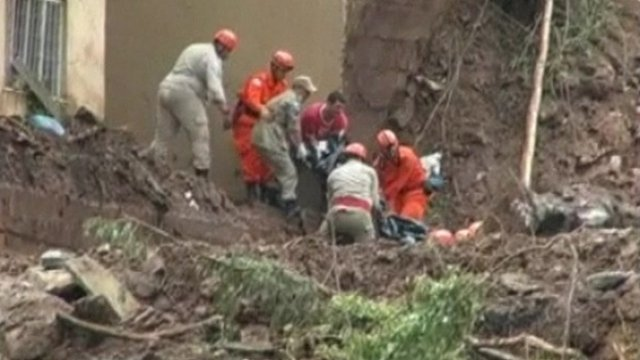 People try to rescue survivors from the mud.