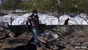 Workers clean up a camp which housed people displaced by the 12 January 2010 earthquake for almost two years, in Port-au-Prince January 10, 2012.