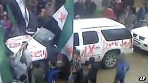 "Image made from amateur video purportedly showing graffiti on an Arab League observer vehicle reading ""Leave"" in al-Hasaka, Syria"