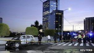 Police officers work at a crime scene where the dead bodies of two men, left inside a burning vehicle, were found near a mall on the outskirts of Mexico City 11 January, 2012