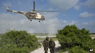 In this Wednesday, Dec. 14, 2011 file photo, two Kenyan army soldiers shield themselves from the downdraft of a Kenyan air force helicopter as it flies away from their base near the seaside town of Bur Garbo, Somalia.