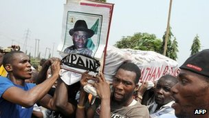 "Protesters carrying mock coffin of President Goodluck Jonathan reading ""Rest in Pains"""