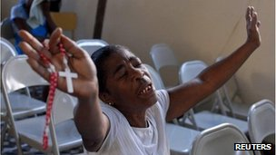 A woman prays during a church service to mark the second anniversary of the 2010 earthquake in Port-au-Prince January 12, 2012