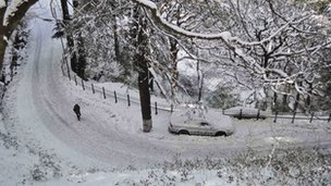 A man walks on a snow-covered road after heavy snowfall in Shimla, India, Thursday, Jan. 12, 2012.