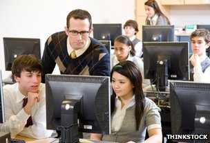 Teacher and teenage pupils in computer lab