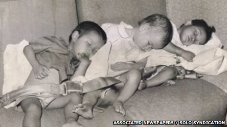 Lê Thanh (L) asleep on the plane with other orphans  as they are airlifted out of Vietnam