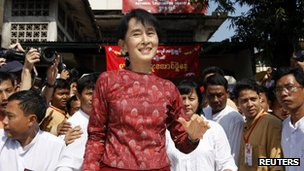 Burma pro-democracy leader Aung San Suu Kyi waves to her supporters as she leaves the National League for Democracy head office on 4 January 2012