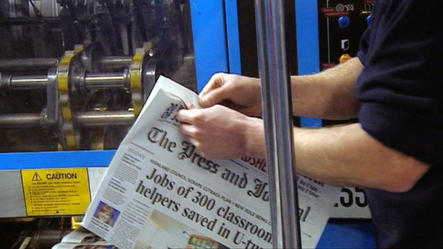 Man picks up a broadsheet copy of the Press and Journal from the printing press