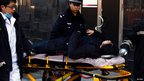 A woman who was dragged away by the police after she refused to leave the Apple store is taken to an ambulance on a stretcher in the Beijing district of Sanlitun, 13 January 2012