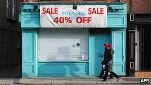 Pedestrians walk pass a closed store advertising a sale in Dublin