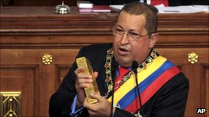Venezuelan President Hugo Chavez brandishes a gold bar as he addresses the National Assembly in Caracas