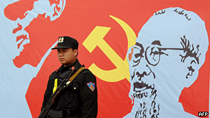 Policeman stands guard with poster of ruling Communist party