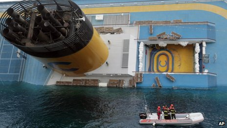 Italian divers approach the cruise ship Costa Concordia leaning on its side, 15 January