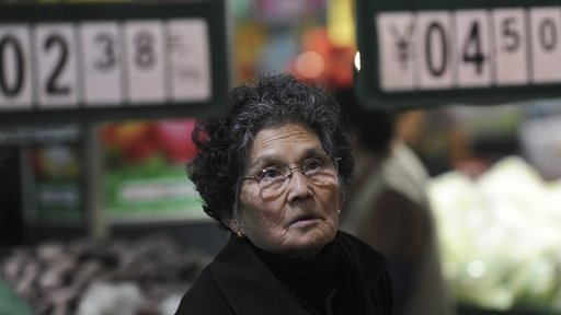 A Chinese woman looks at the price of vegetables