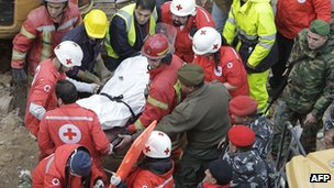 Lebanese rescue workers remove a body from the site of a collapsed building in Beirut, Lebanon, on 16 January 2012