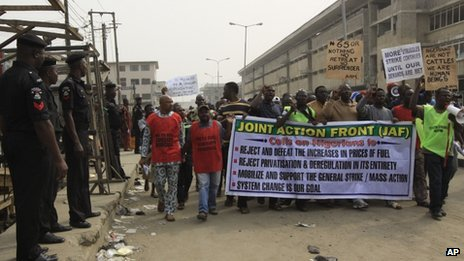 Policemen stand guard as angry youths protest on a street in Lagos, Nigeria, Monday, 16 January, 2012.
