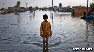 A boy makes his way through flood waters in a village south of Muzaffargarh in Punjab, 21 August 2010