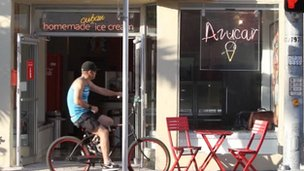 A man cycles past the storefront