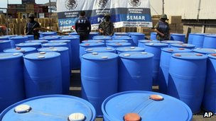 In this photo released by the Mexican navy on 28 December 2011, Navy marines stand guard in front of several barrels containing methylamine, a controlled substance used as a precursor to methamphetamine, that were inside several containers headed for Guatemala, seized at the Pacific port of Lazaro Cardenas