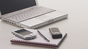 A laptop, mobile phone and notepad