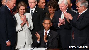 President Obama clapping, surrounded by supporters of the Dodd-Frank act