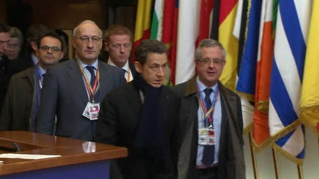 Sarkozy surrounded by officials