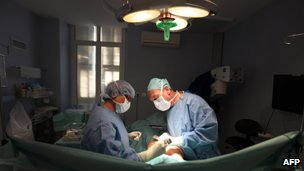 Two surgeons removing PIP implant
