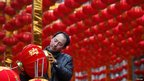 A man checks a red lantern as he stands in front of the decorations for the upcoming Chinese New Year in Lanzhou, Gansu, 19 January 2012