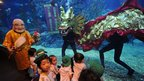 Children look on as scuba divers perform an underwater dragon dance as part of the Lunar New Year celebrations at Siam Ocean World in Bangkok, 17 January 2012