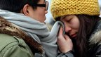A young woman wipes her tears with her partner's scarf as they part at Beijing West Railway Station, 19 January 2012