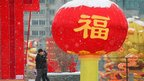 A couple kiss next to a red lantern decoration for the upcoming Chinese New Year amid snowfall in Lanzhou, Gansu province, 20 January 2012