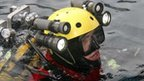 A scuba diver belonging to the firefighting team stands in the waters near the Costa Concordia cruise ship
