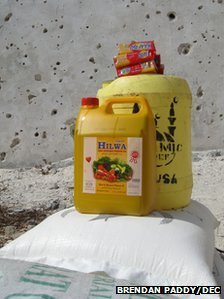 A pile of food aid made up of sacks of flour, yellow cooking oil canisters and red sugar packets