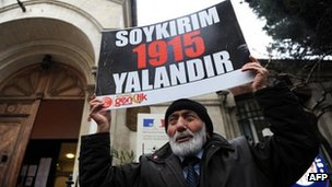 "A Turkish man holds a placard reading ""Genocide is a lie"" in front of the French Consulate in Istanbul, 23 December 2011"
