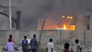 People look at burning police station in Kano. Photo: 20 January 2012