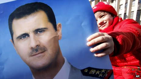 A pro-Syrian regime protester holds a portrait of Syrian President Bashar Assad  in Damascus, Syria, on 20 January 2012