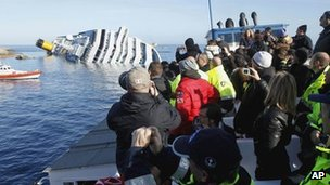 People take pictures of the grounded cruise ship Costa Concordia off the Tuscan island of Giglio, Italy, 21 January 2012