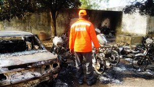 A rescue worker inspects burnt-out wreckage in the Marhaba area of Kano, on January 21