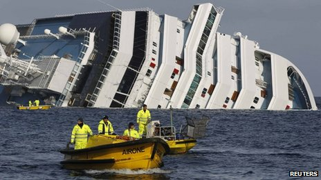Fuel recovery workers pass the Costa Concordia
