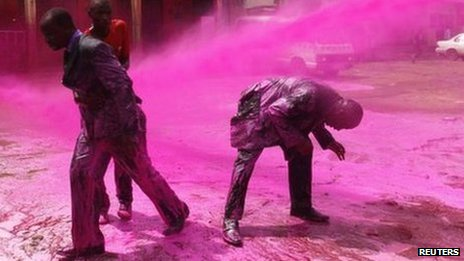 Anti-riot police use water cannons, with pink water, against opposition supporters in Uganda