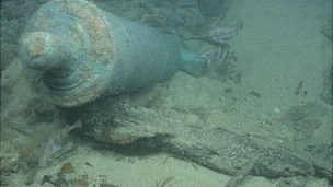 Bronze cannon protruding from a sandbank on the shipwreck site of HMS Victory