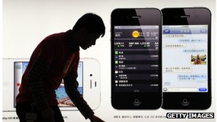 A consumer looks at an iPhone poster in China